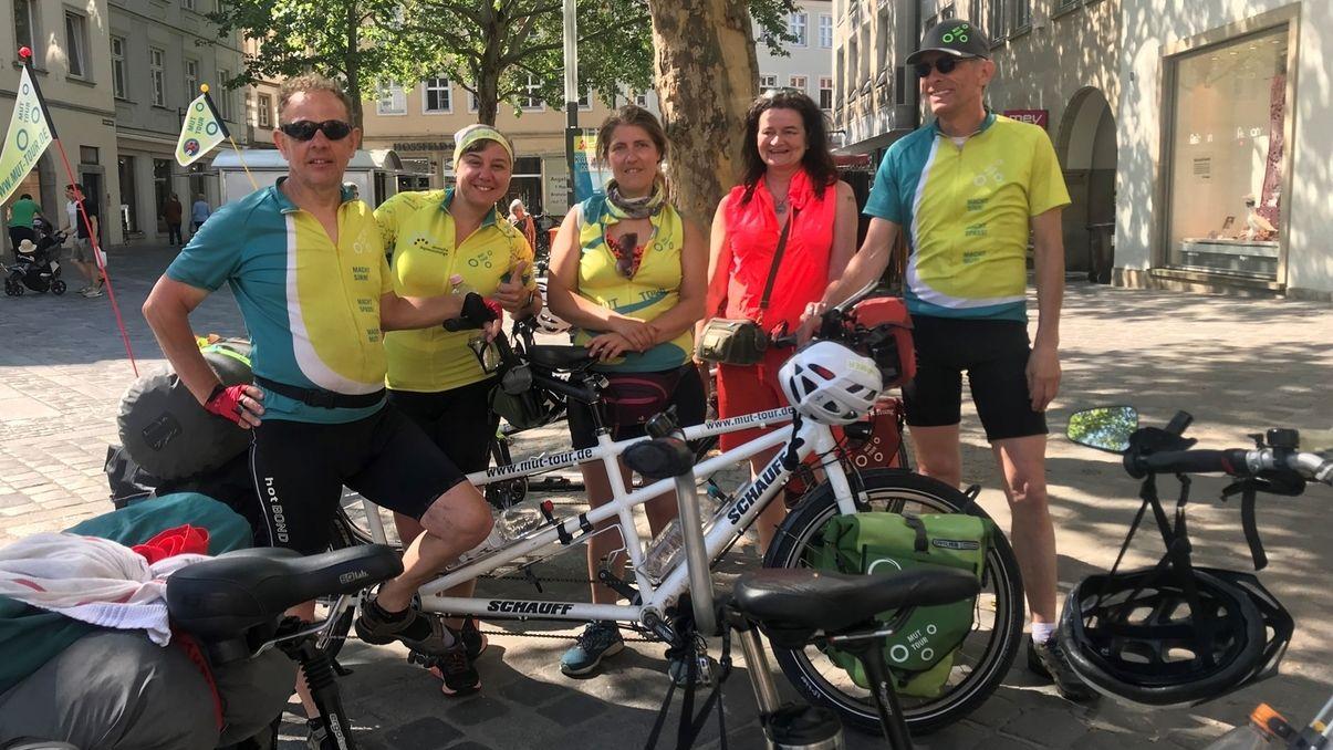 Die Tandemfahrer der Mut-Tour stehen als Gruppe hinter ihren Rädern