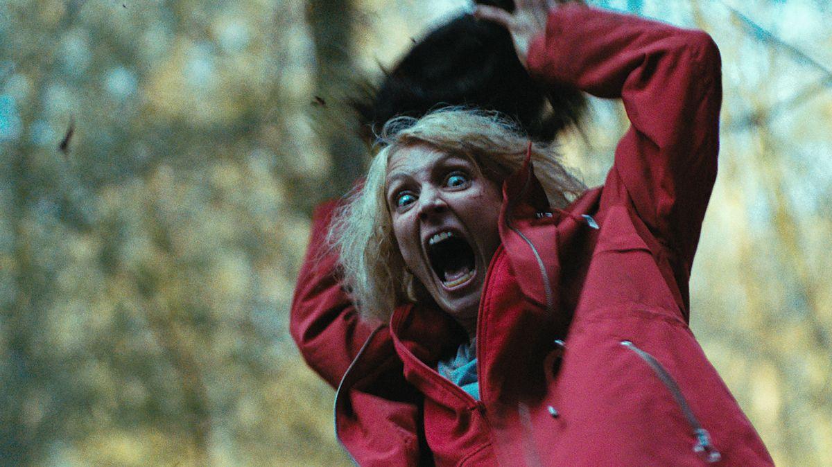 Eve im roten Mantel reißt mit verzerrtem Gesicht Stein in die Höhe.