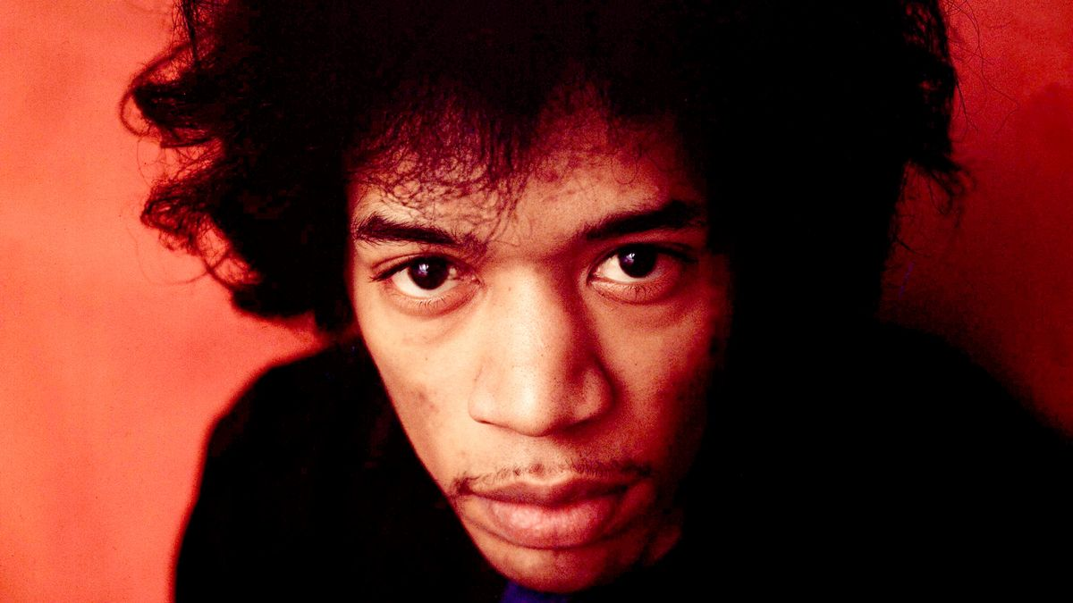 Jimi Hendrix (mit Menjou-Bärtchen) vor rotem Hintergrund, blickt direkt in die Kamera.