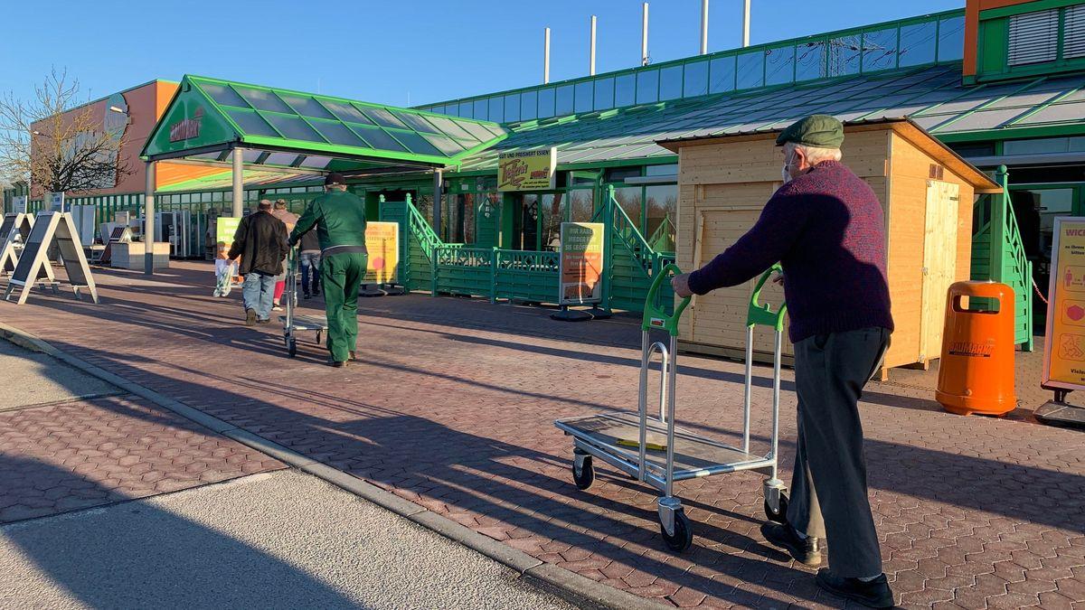 Kunden am Montagmorgen vor einem Regensburger Baumarkt.