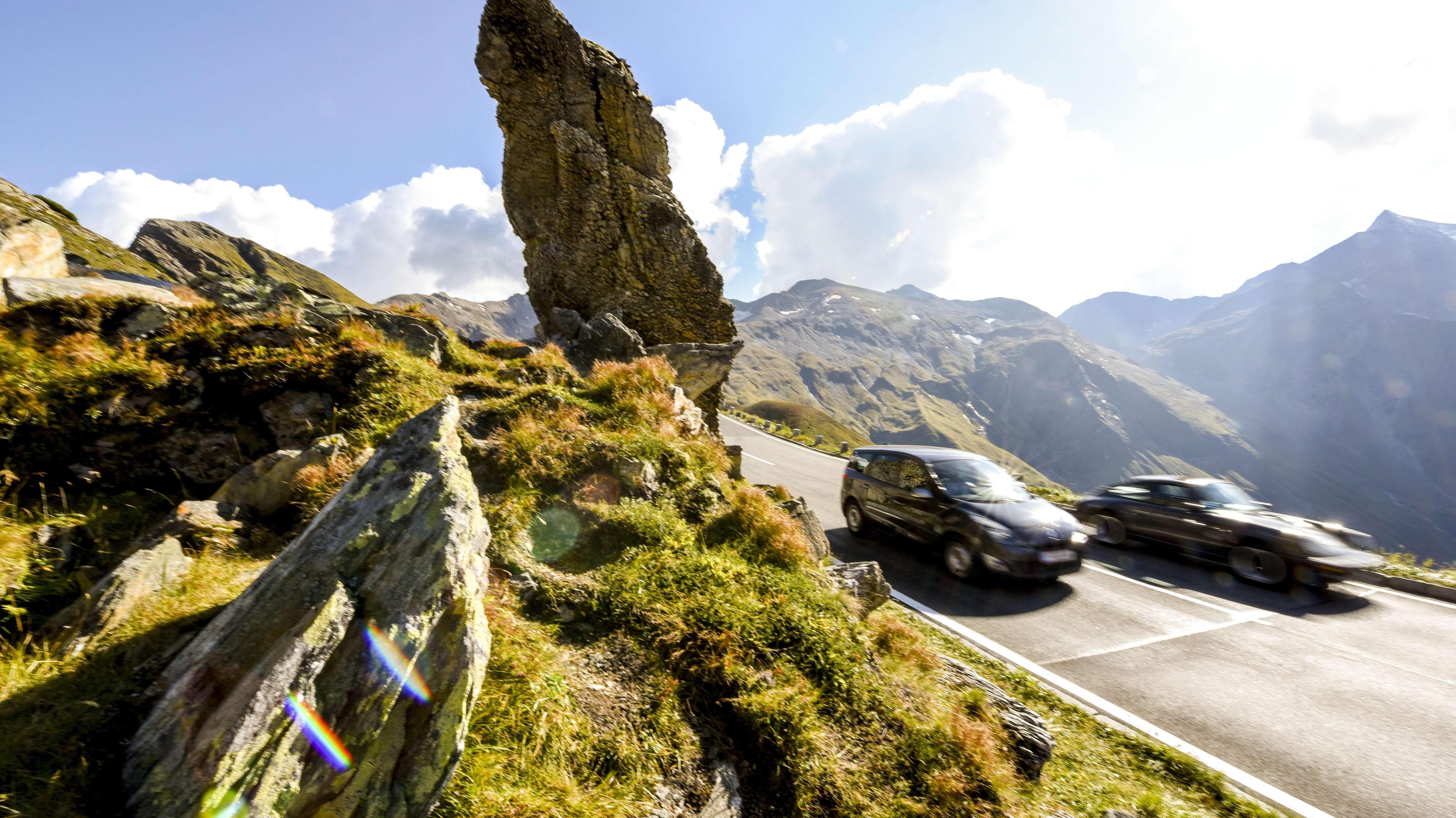 Autos in den Alpen: zwei schnelle Fahrzeuge beim Großglockner in Österreich. Straßenverkehr macht einen der größten Anteile beim CO2-Ausstoß aus.