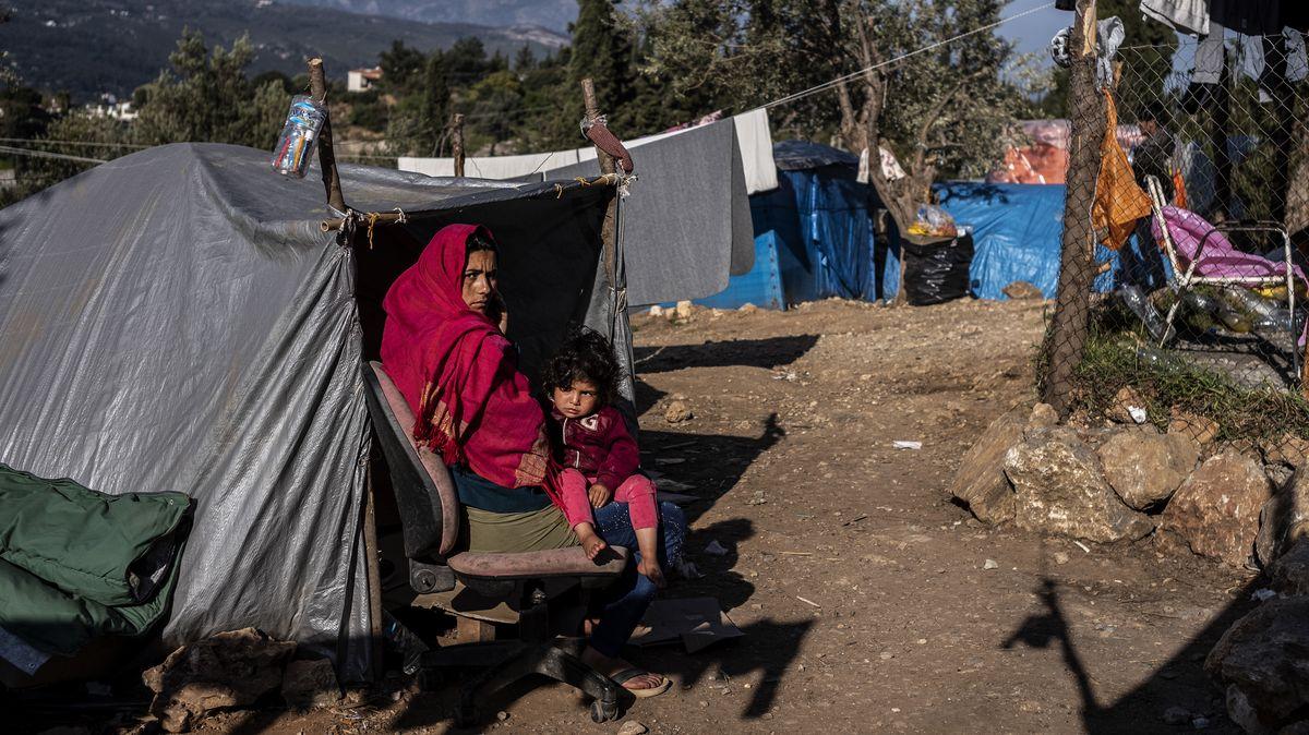 Eine Frau und ein Kind sitzen vor einem provisorischen Zelt in einem Flüchtlingscamp.