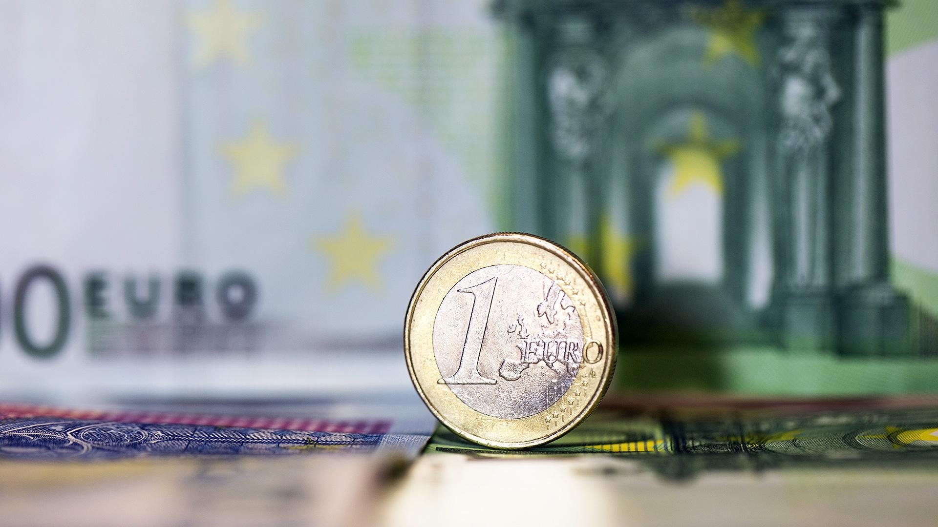 Eine Ein-Euro-Münze vor einem Hundert-Euro-Geldschein