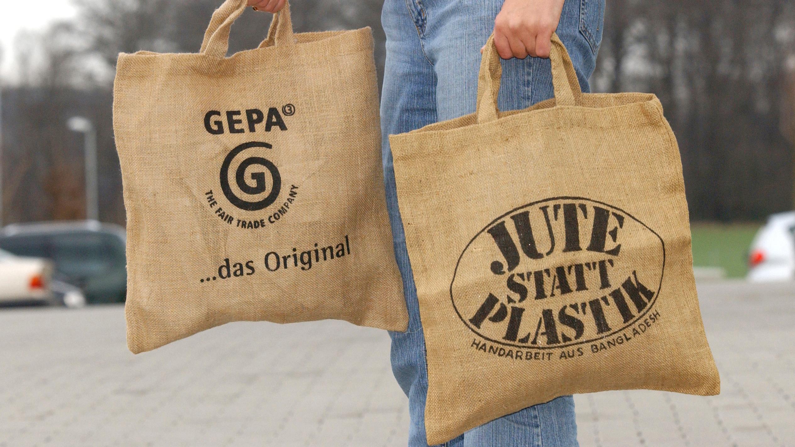 """Ein Mann trägt zwei Jutetaschen mit der Aufschrift """"Jute statt Plastik"""""""