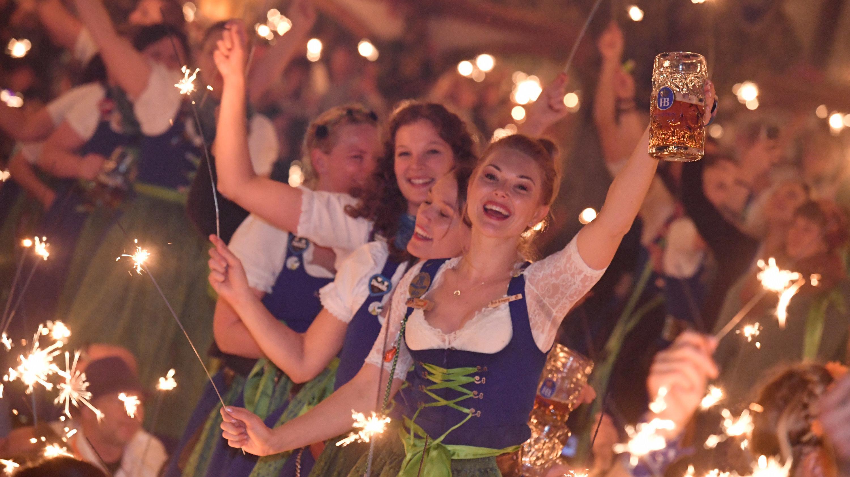 06.10.2019, Bayern, München: Bedienungen stehen im Hofbräu-Zelt beim traditionellen Kehraus auf den Tischen, halten dabei Wunderkerzen in den Händen und feiern damit das Ende der harten Arbeit auf der Wiesn.