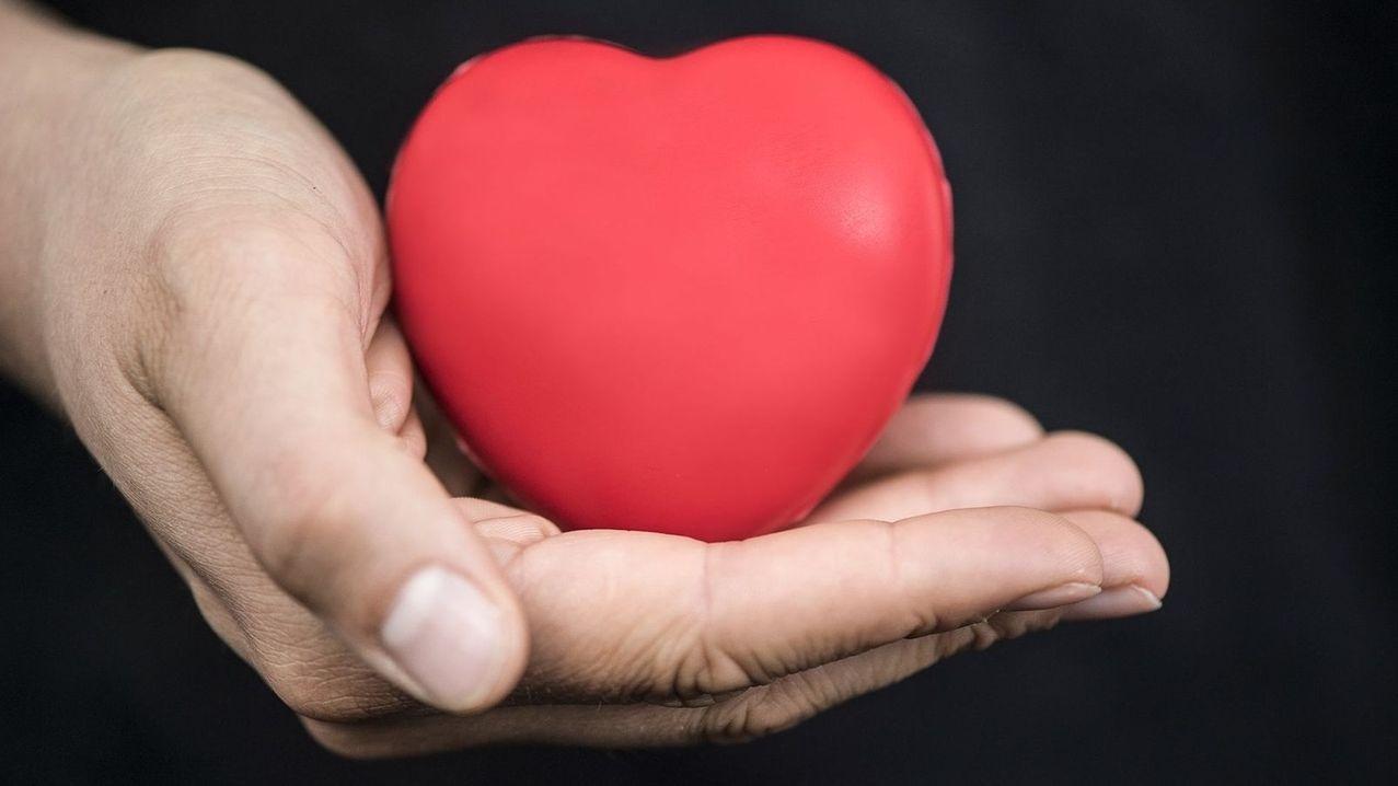 Ein Hand hält ein rotes Plastikherz.