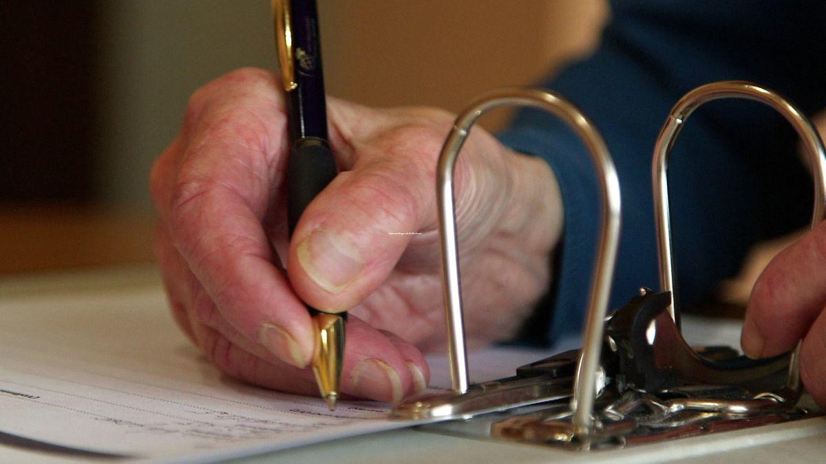 Eine Seniorin unterschreibt ein Dokument