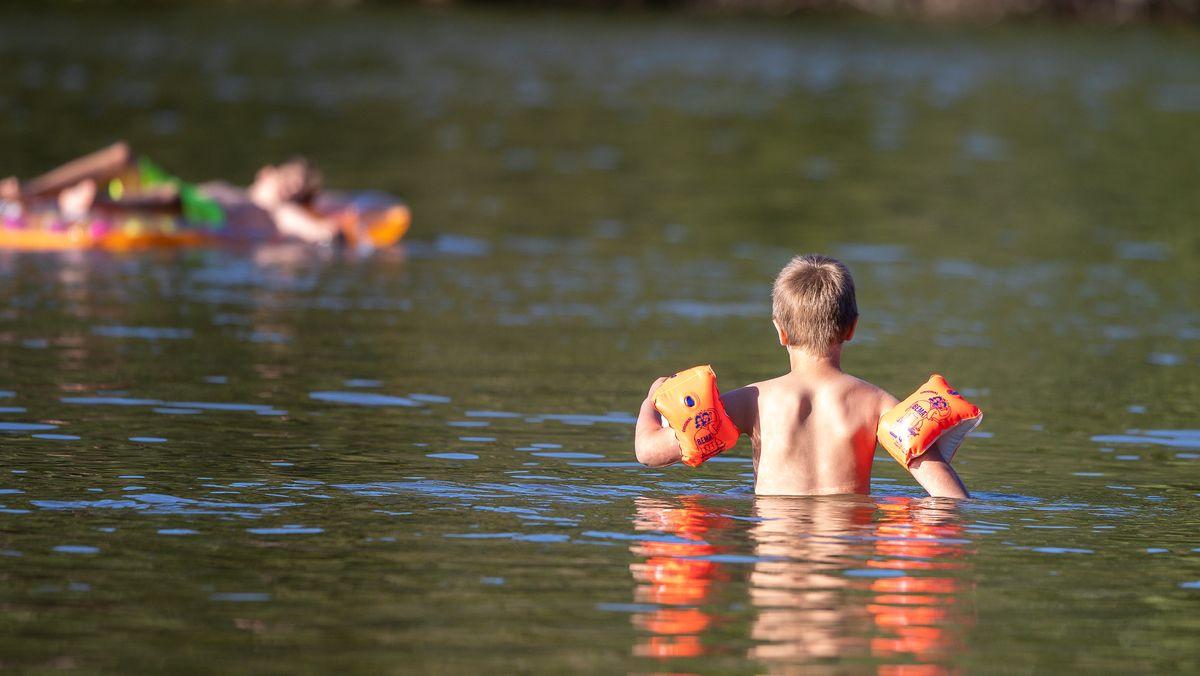 Kind mit Schwimmflügeln in einem Bdesee