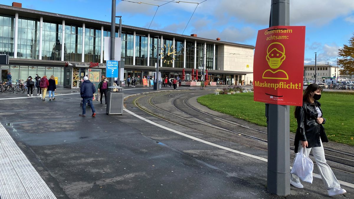 Auf dem Würzburger Bahnhofsvorplatz gilt eine Maskenpflicht. Schilder weisen darauf hin.