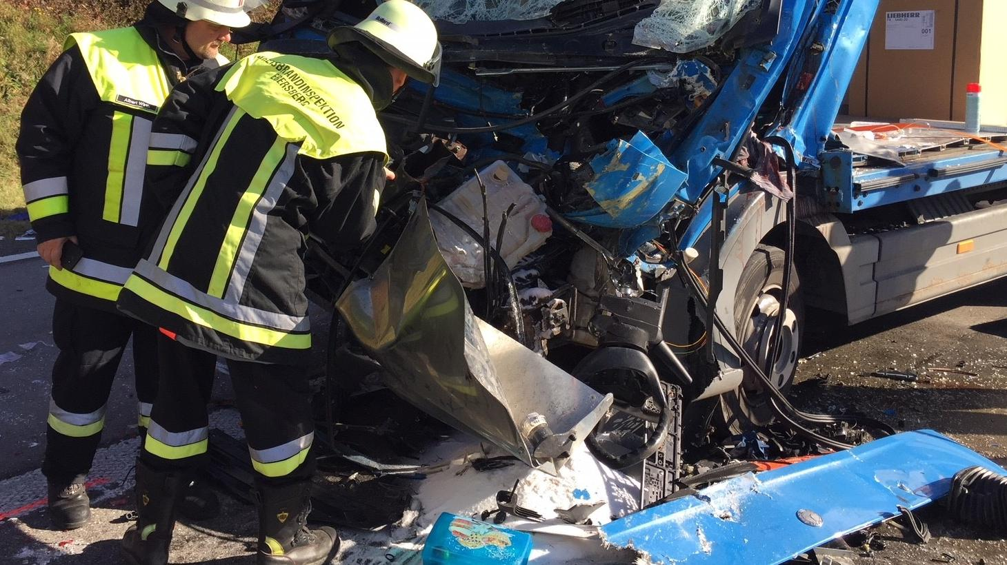 Zwei Feuerwehrleute stehen vor dem Wrack eines der drei in den Unfall verwickelten Lkws.