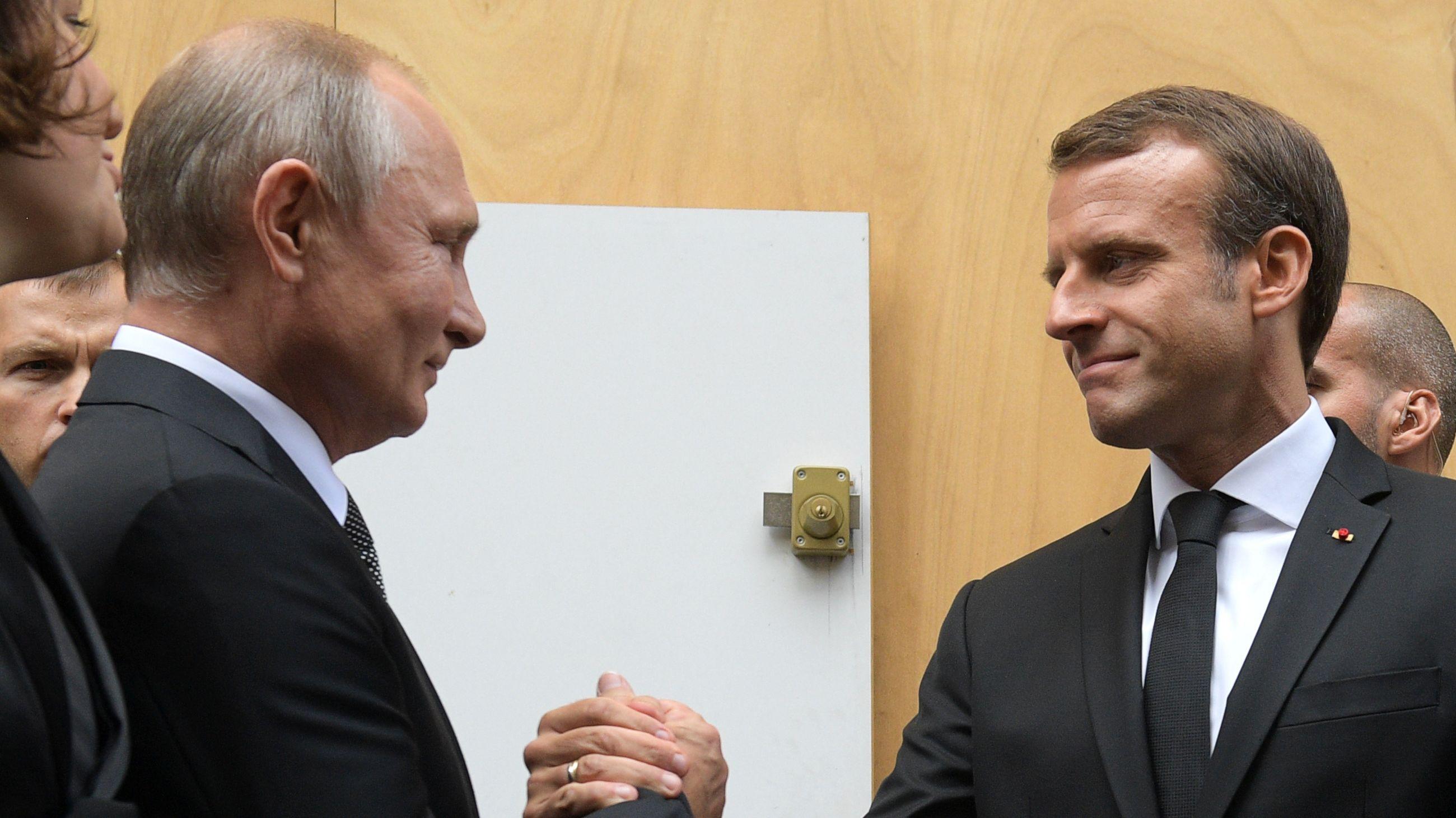 Russlands Präsident Vladimir Putin (L) schüttelt Frankreichs Präsident Emmanuel Macron die Hand nach einer Gedenkveranstaltung für den französischen Ex-Präsidenten Jacques Chirac.