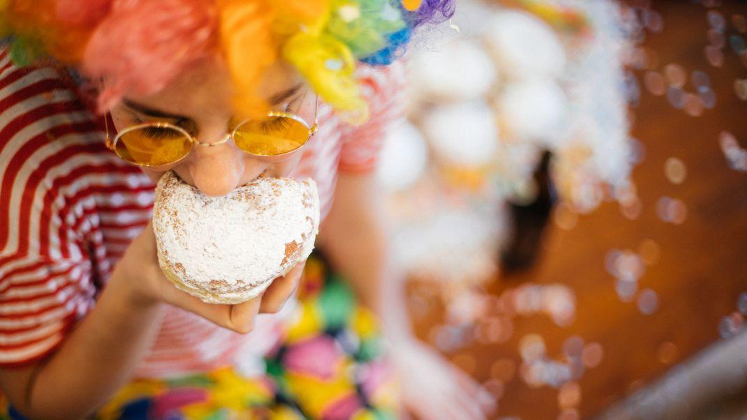 Eine verkleidete Frau isst einen Krapfen.