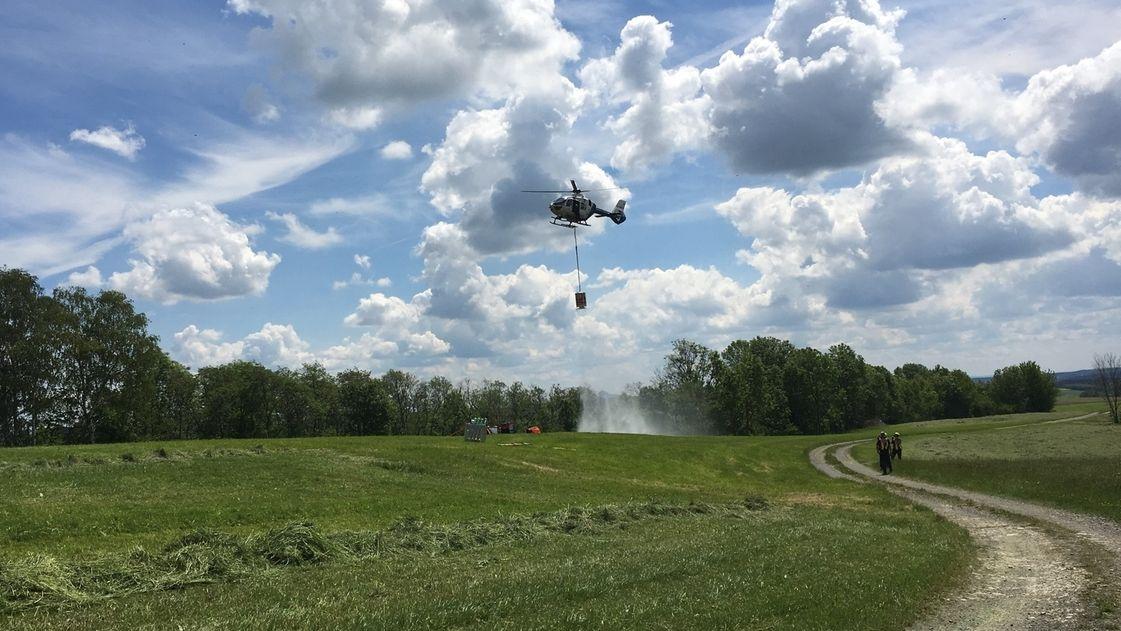 Ostbayerische Flughelfer trainieren das Löschen von Waldbränden. Aus einem Hubschrauber schütten sie Wasser auf eine Wiese.
