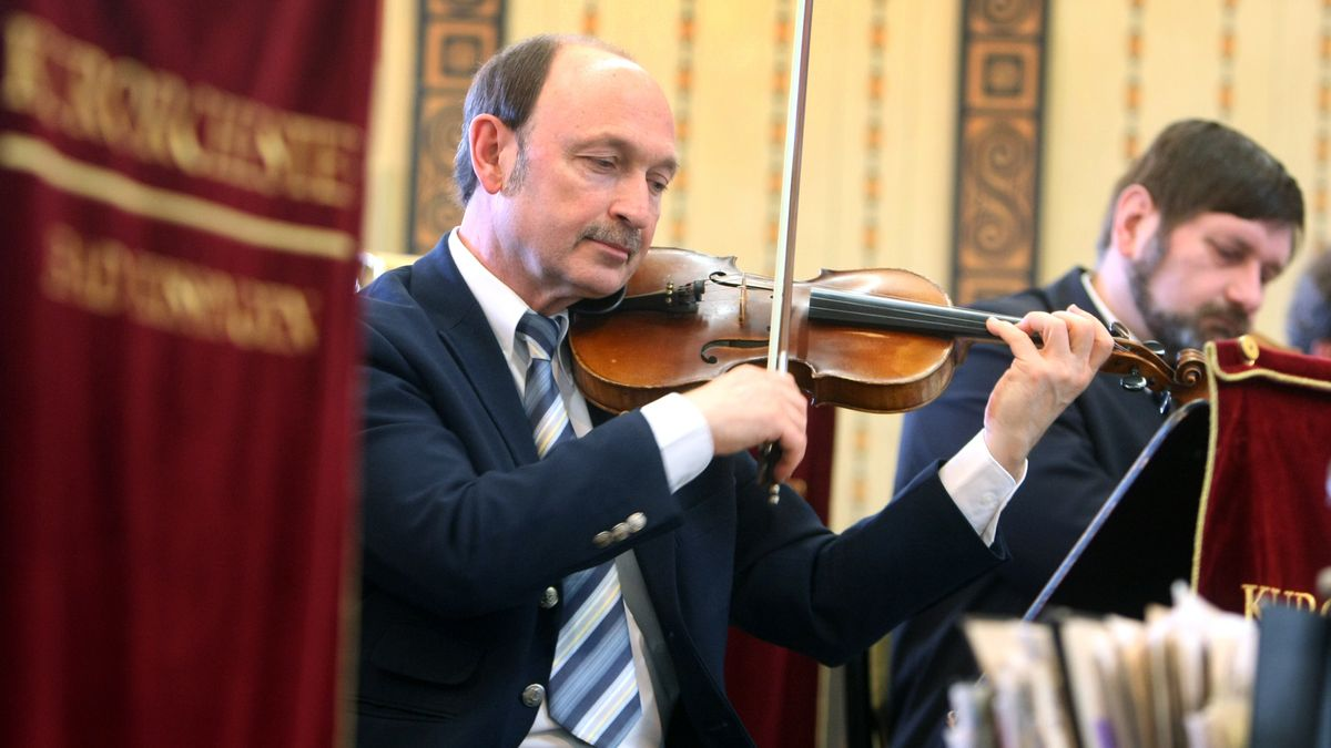 Musiker legt den Bogen an sein Instrument