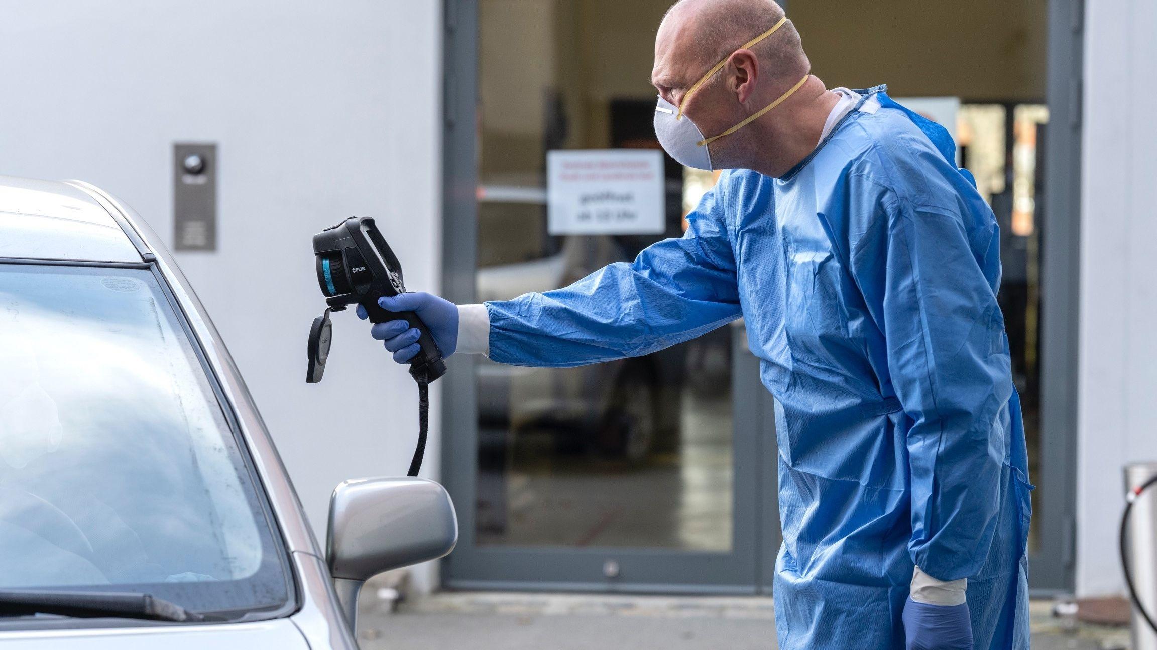 Ein Mitarbeiter der Teststelle Hof im blauem Schutzanzug hält eine Wärmebildkamera durch das geöffnete Fenster in Richtung Testperson, die im Auto sitzt.