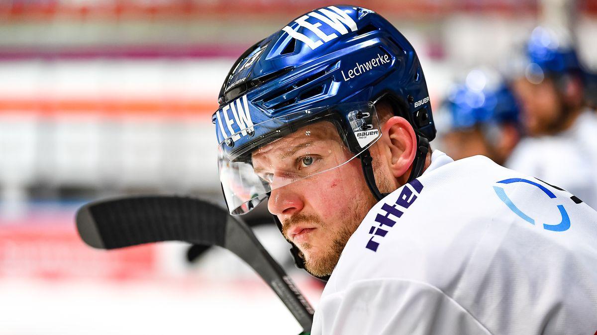 Steffen Hölzer sitzt am Spielfeldrand mit dem Eishockeyschläger in der Hand