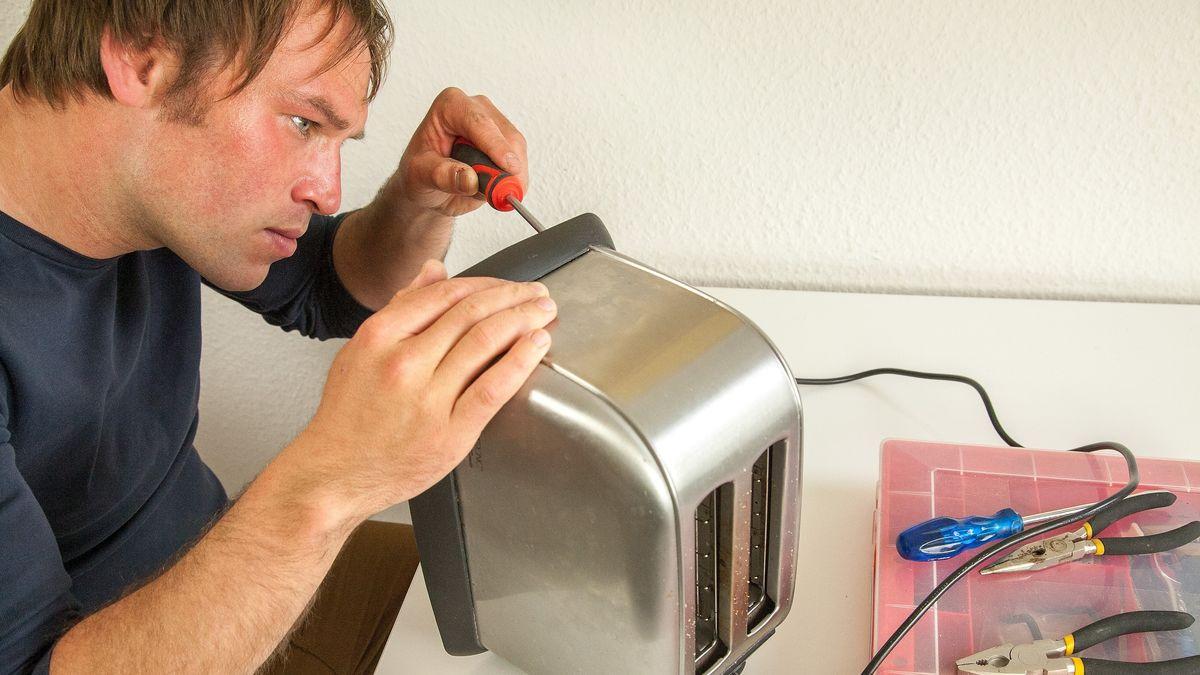Ein Mann repariert einen Toaster.