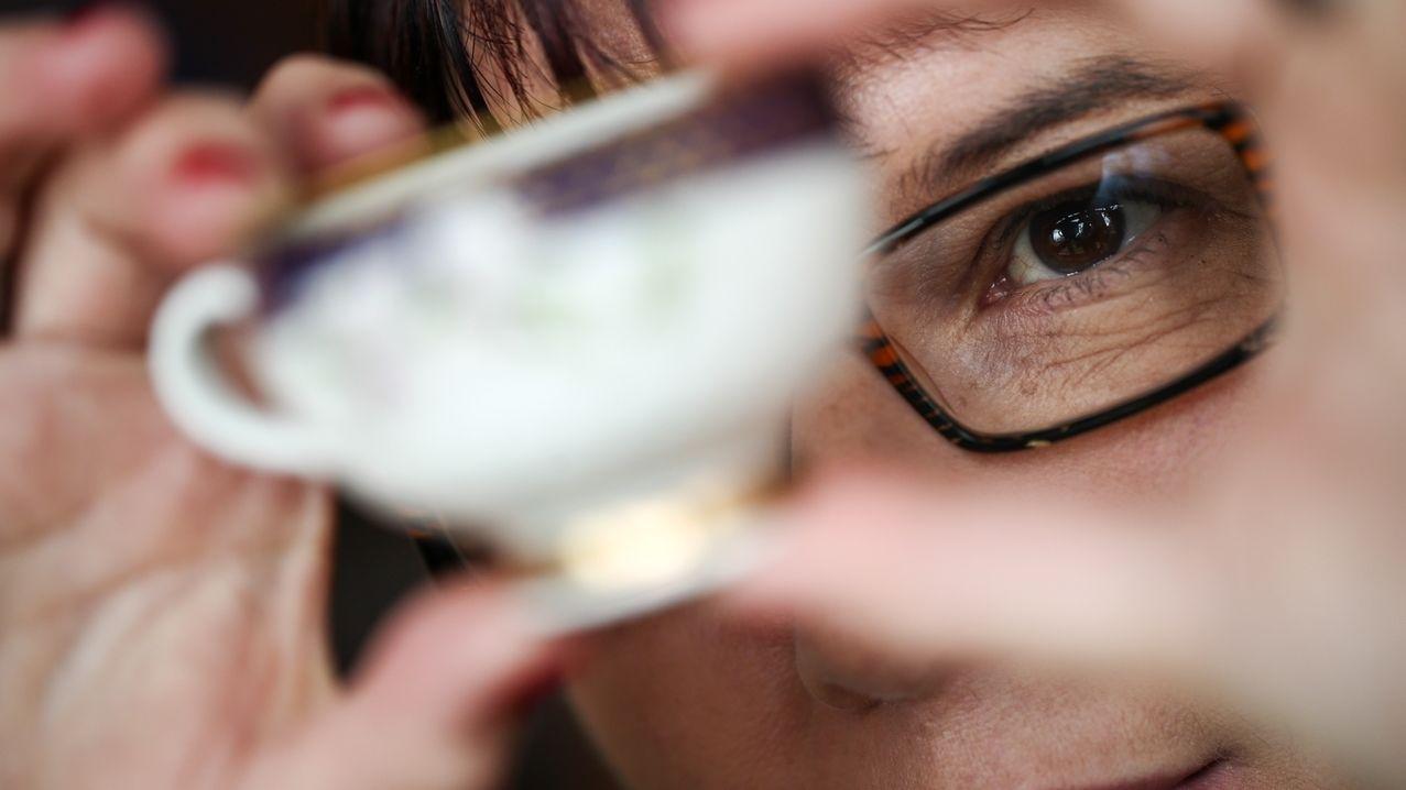 Eine Frau mit Brille betrachtet eine Porzellantasse genau.