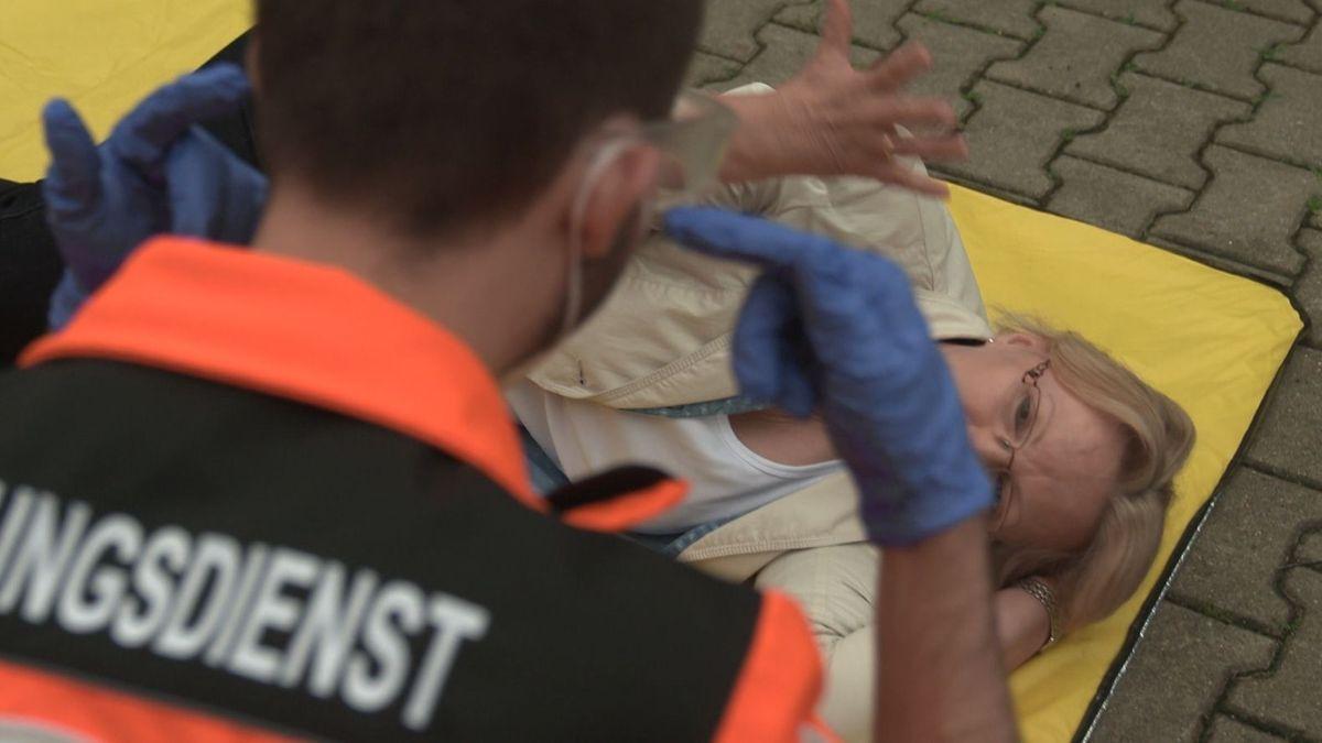 Ein Rettungssanitäter hilft bei einer Übung einer gehörlosen Frau, die am Boden liegt