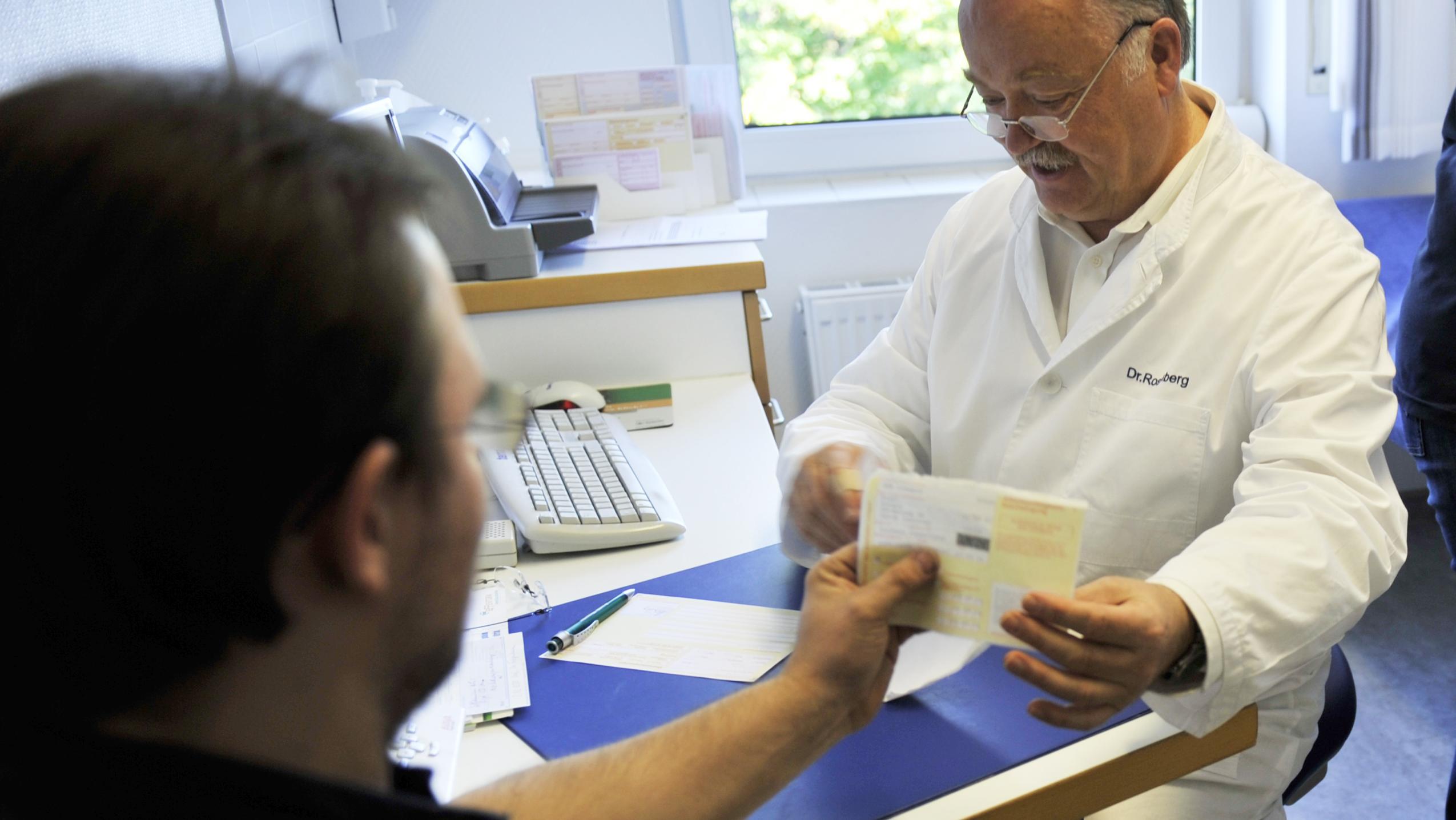 Ein Arzt gibt einem Patienten eine Arbeitsunfähigkeitsbescheinigung in die Hand.