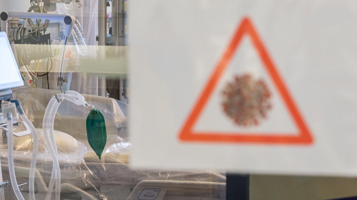 Ein Intensivbett mit Beatmungseinheit steht auf einer Corona-Station hinter einer Scheibe an der ein Achtungssymbol mit einem stilisierten Coronavirus angebracht ist.