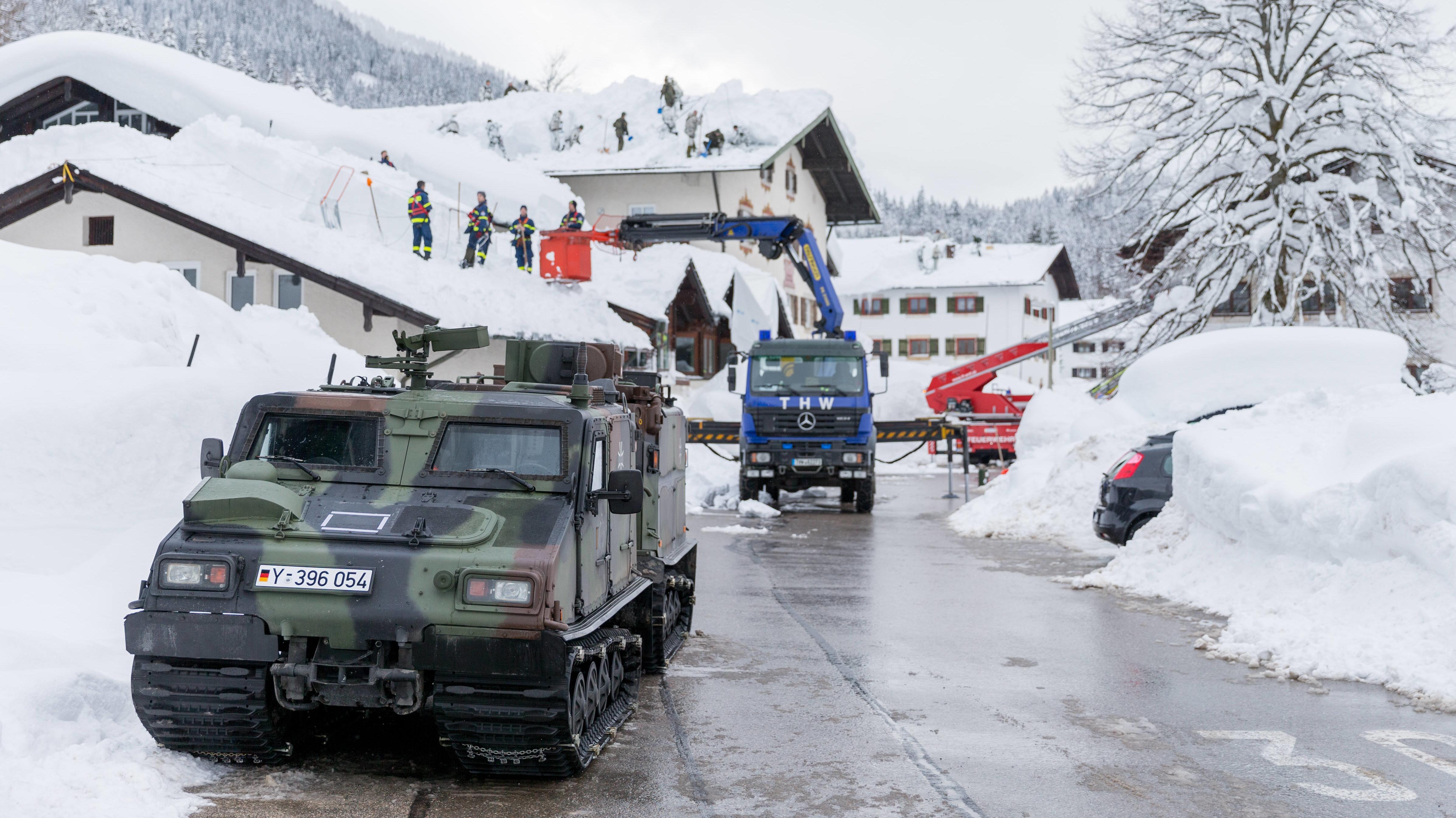 Teams der Gebirgsjägerbrigade 23, des Technischen Hilfswerks und der Feuerwehr Schnee räumen Schnee von Hausdächern im Berchtesgadener Land.