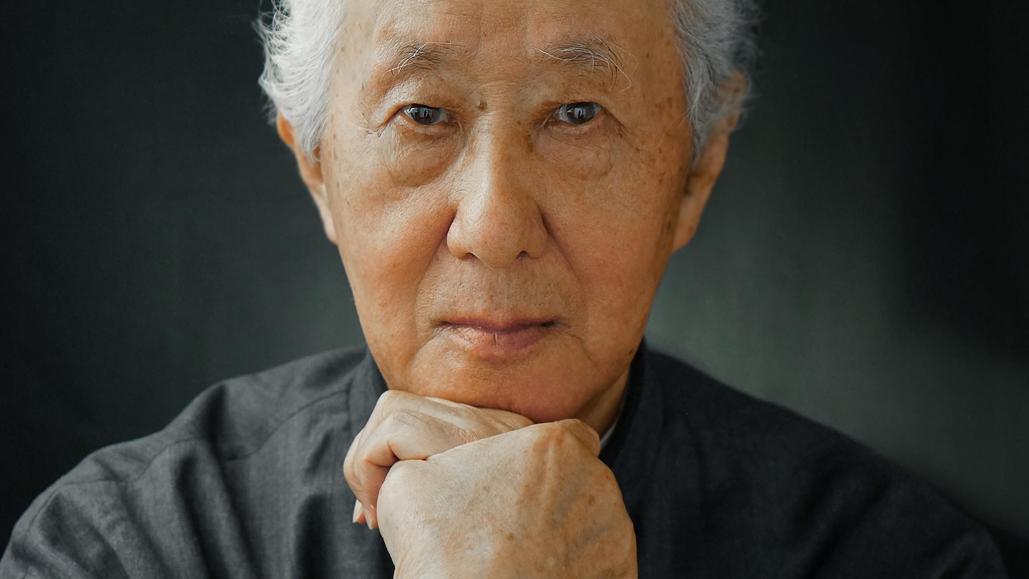 Der japanische Architekt Arata Isozaki blickt über zusammengelegten Händen in die Kamera.