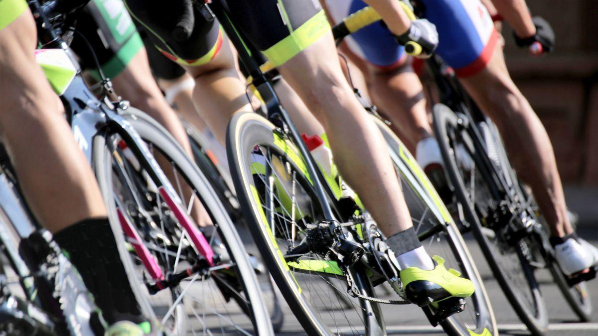 Muskulöse Beine von Radrennfahrern auf dem Rennrad.