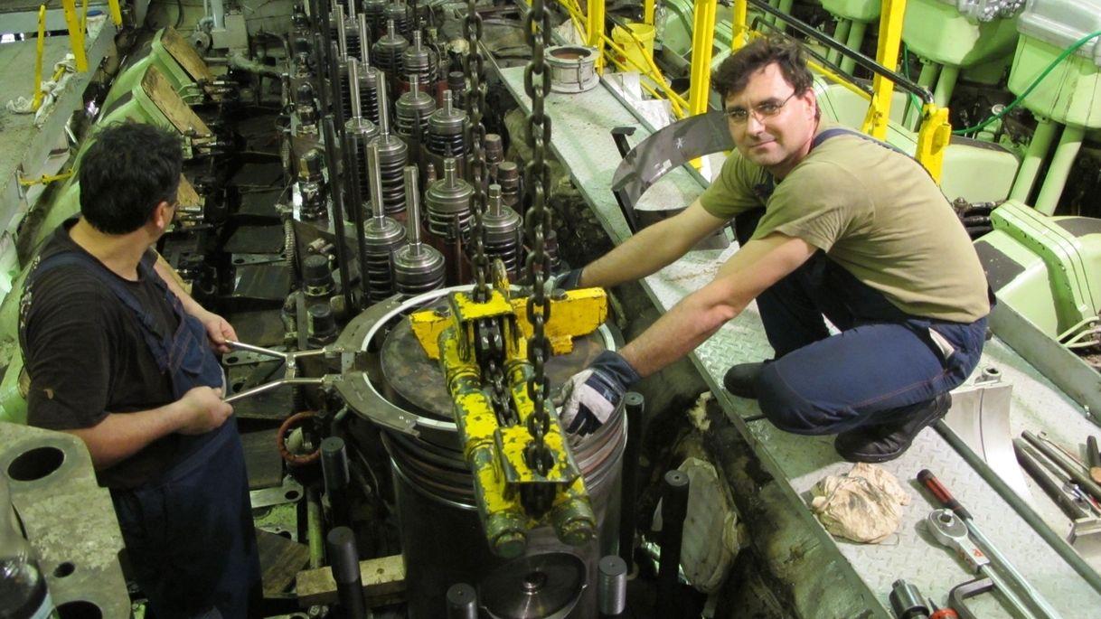 Im Maschinenraum arbeiten Mechaniker an einem Schiffsmotor (Symbolbild)