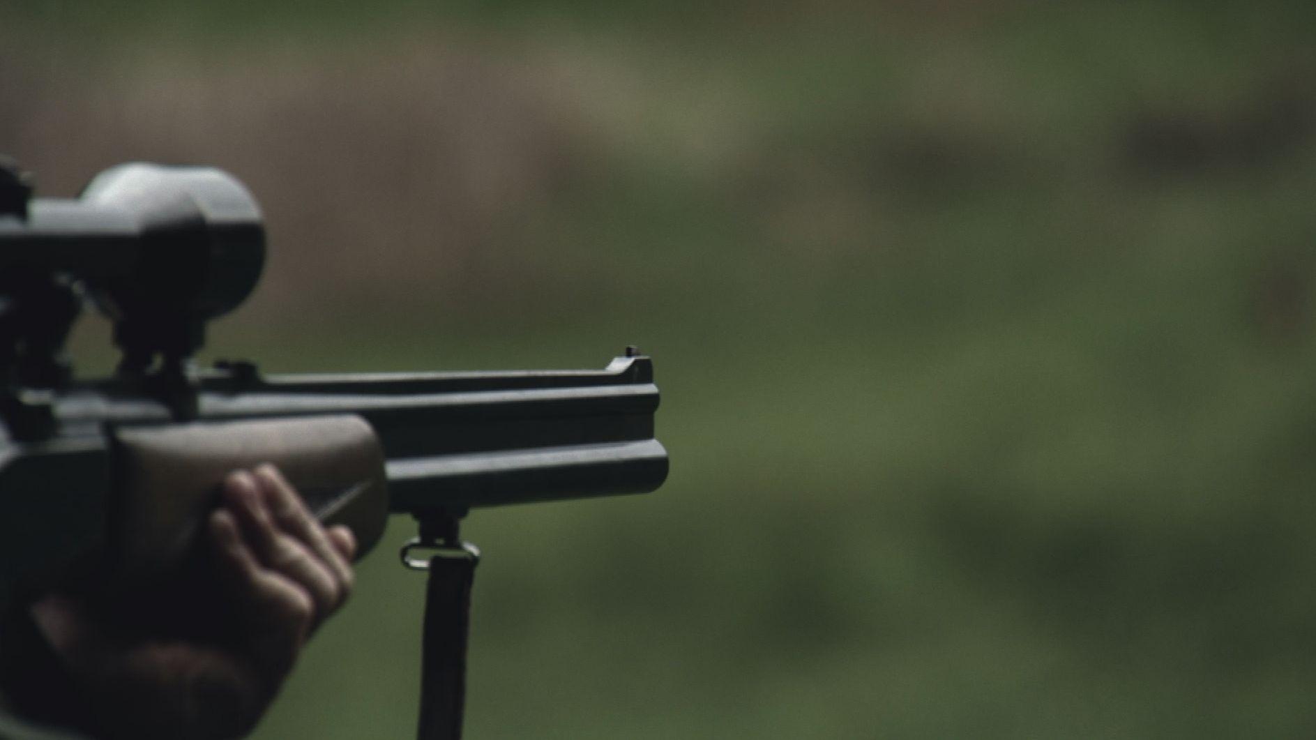 Der Lauf eines Gewehrs mit Zielfernrohr ragt von links ins Bild.