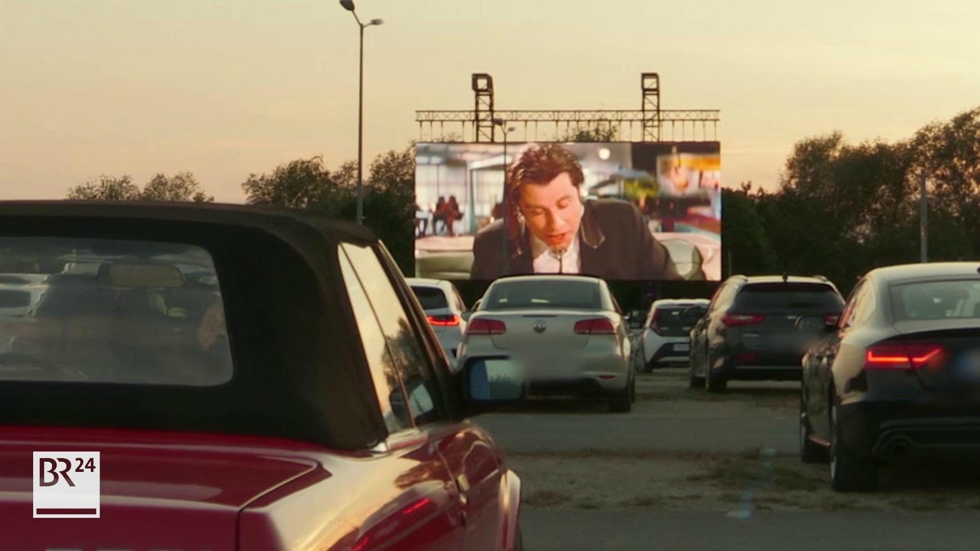 """Autos vor einer Leinwand, auf der John Travolta in """"Pulp Fiction"""" zu sehen ist"""