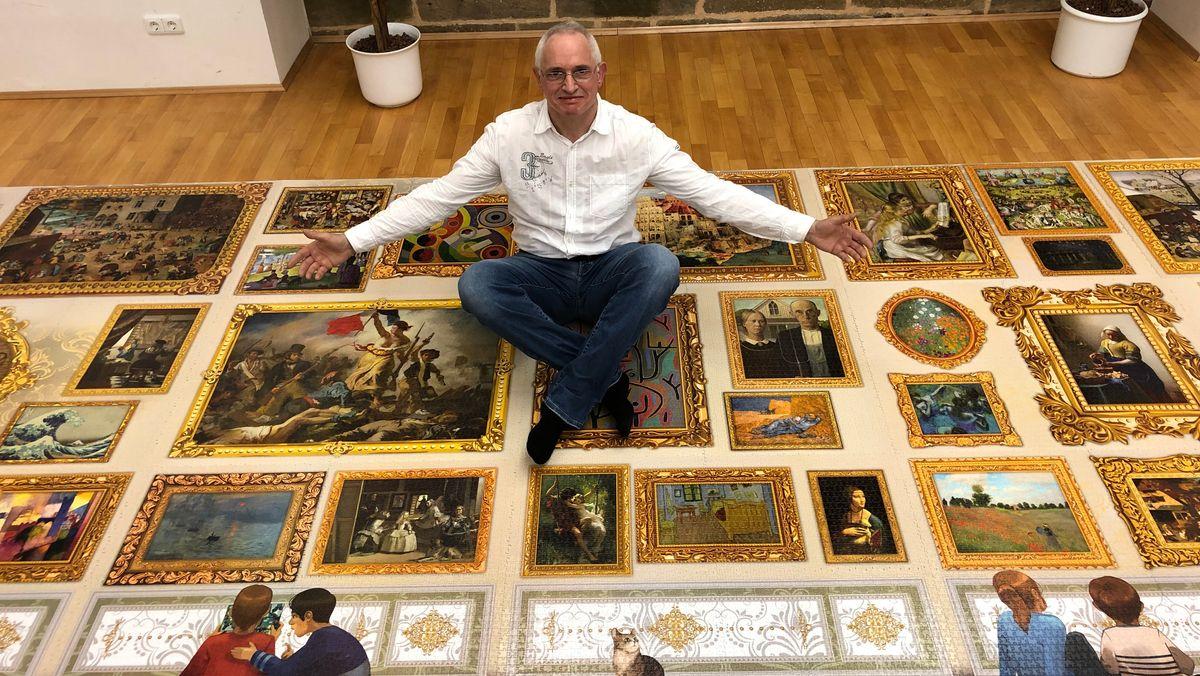 Weltrekordhalter Peter Schubert sitzt auf seinem aus 54.000 Teilen gefertigten Puzzle.