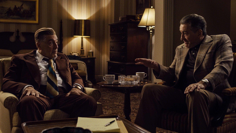 """Al Pacino als Jimmy Hoffa und Robert de Niro als Frank Sheeran unterhalten sich in einem Arbeitszimmer bei Kaffee und Zigaretten in """"The Irishman""""."""