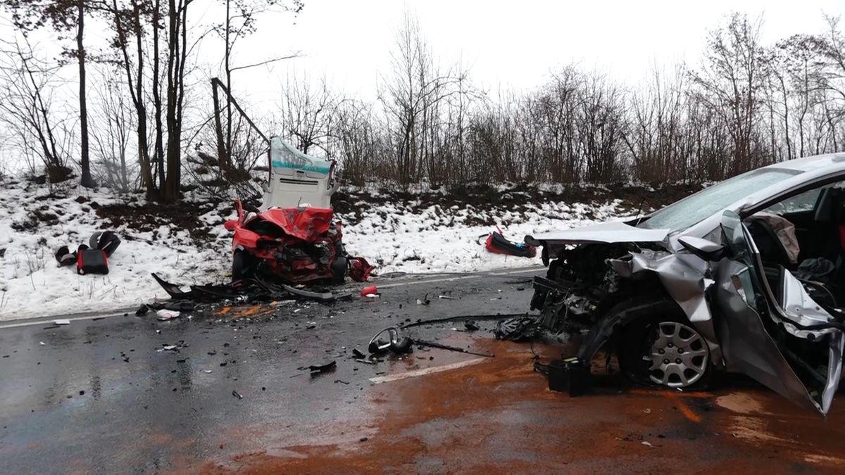 Zwei zerstörte Autos und Scherben auf einer Straße.
