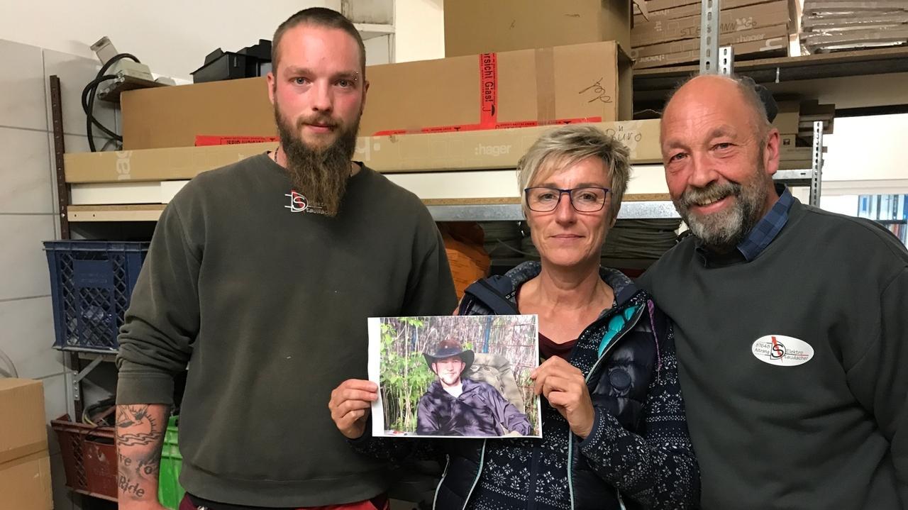 Lukas, Sieglinde und Christian Staudacher mit einem Foto von Aman Mohammadi in der Werkstatt ihres Betriebs in Aitrang.