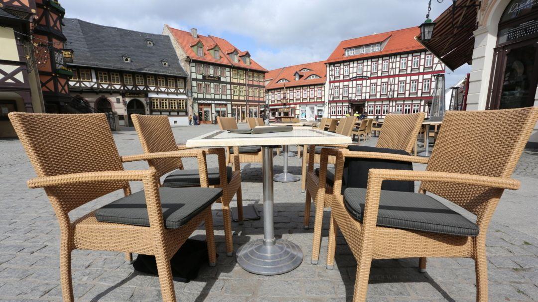 Auf dem Marktplatz in Wernigerode (Sachsen-Anhalt) stehen leere Tische und Stühle vor einem Café.