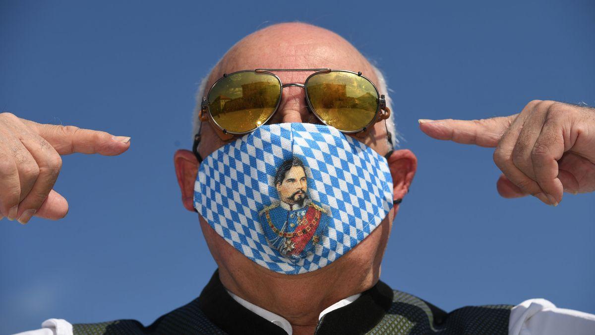 Der Geschäftsführer von Angermaier Trachten, Axel Munz, trägt eine blau-weiße Trachtenmaske mit König Ludwig-Motiv.