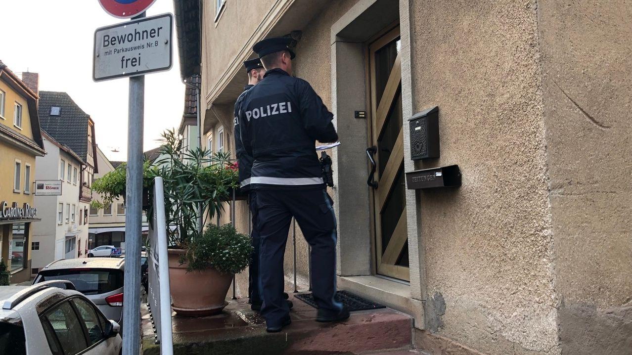 Zwei Polizisten stehen in Hammelburg vor einem Haus.
