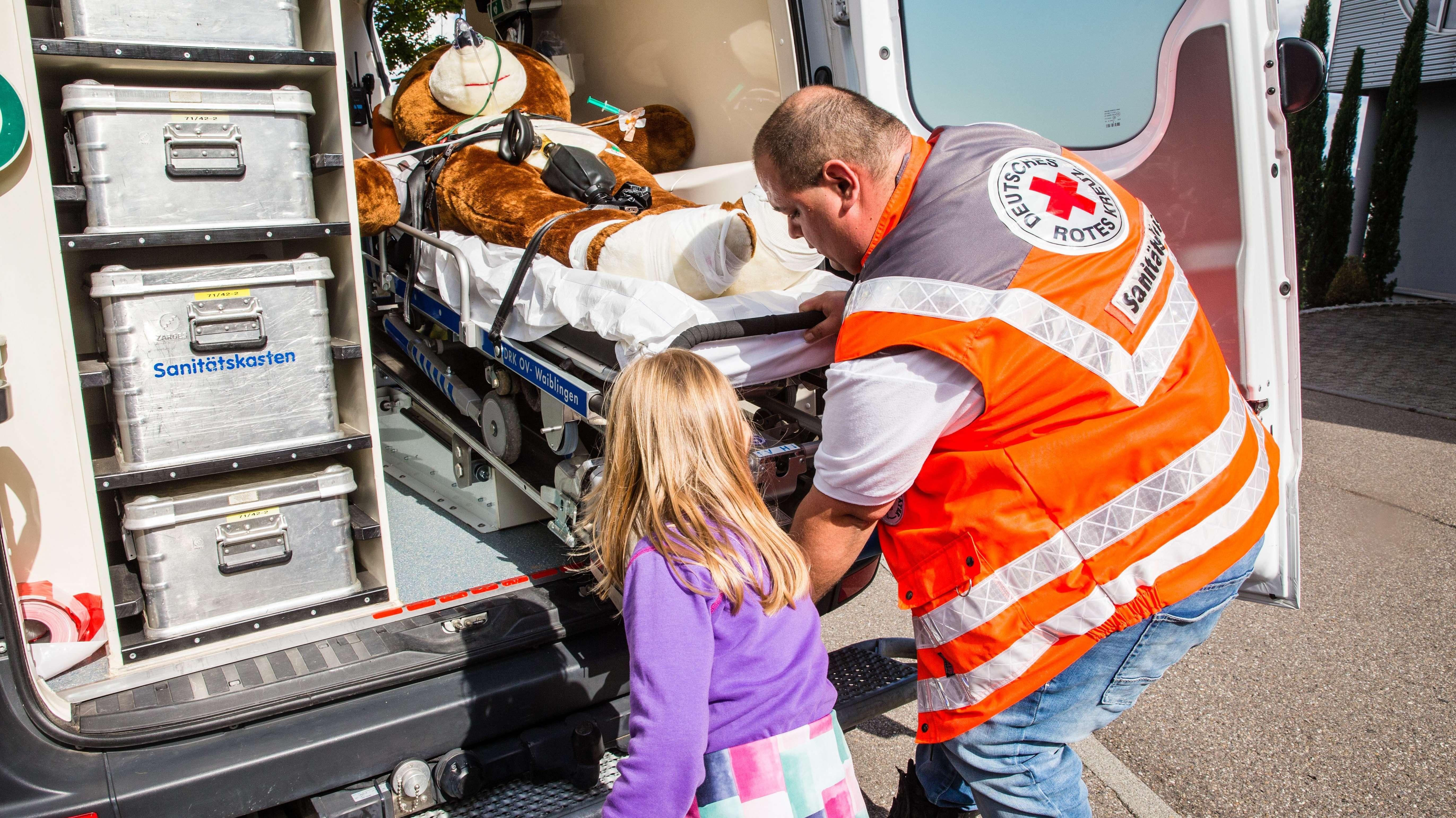 Einem 6-jährigen Mädchen wird mit einem Teddy spielerisch die Arbeit des DRK Rettungsdienstes vermittelt.