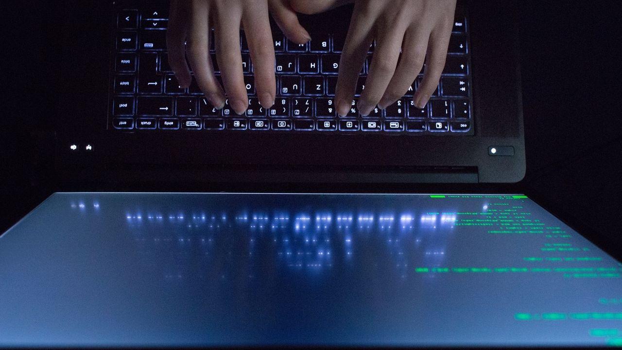 Hände tippen auf einem Laptop mit Programmcode (Symbolbild).