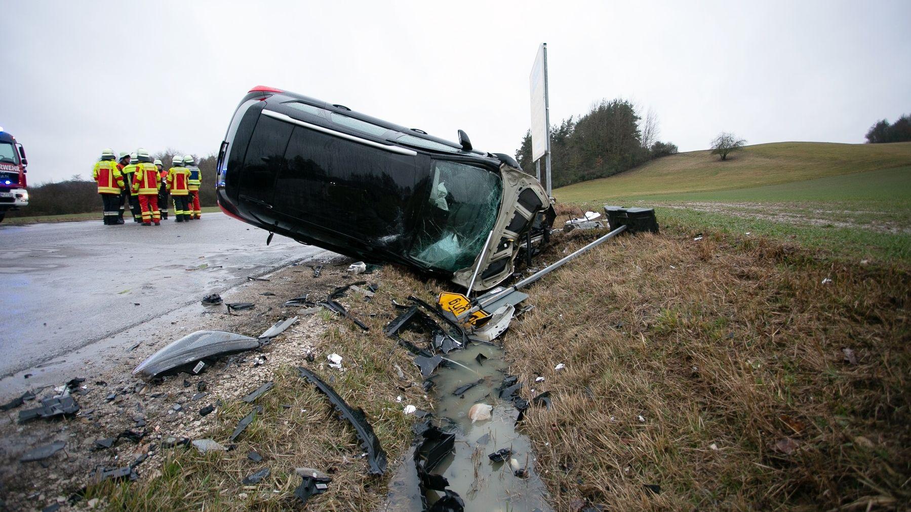 Ein Unfallfahrzeug liegt auf die Seite gedreht in einem Straßengraben.