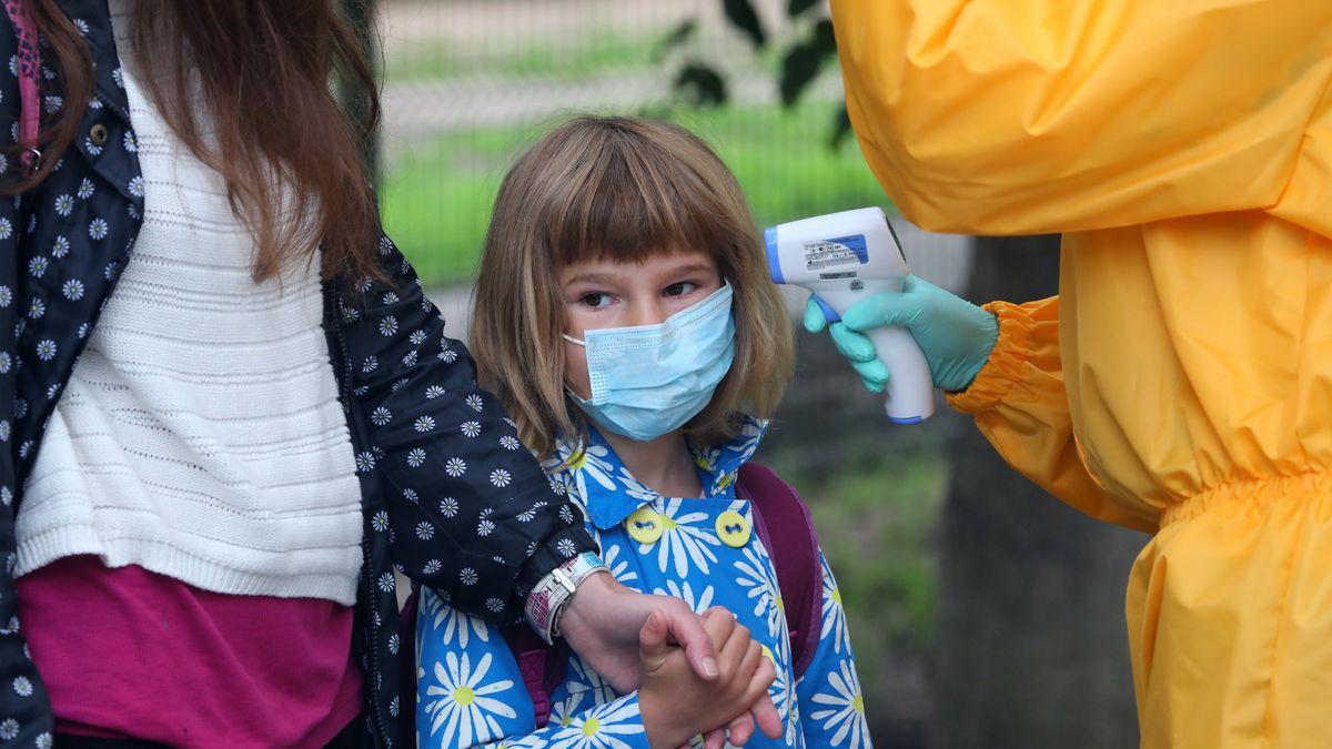 Ein Kind geht an der Hand seiner Mutter und trägt Mundschutz.