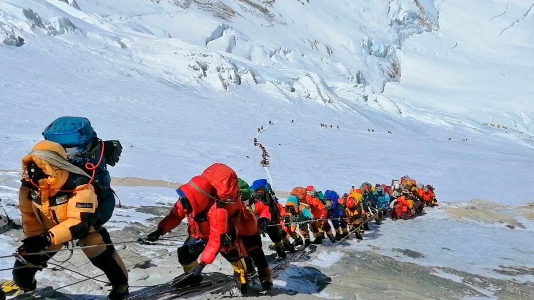 Bergsteiger in bunten Daunenjacken am Seil im Stau auf dem Weg zum Gipfel des Mount Everest (Symbolbild)