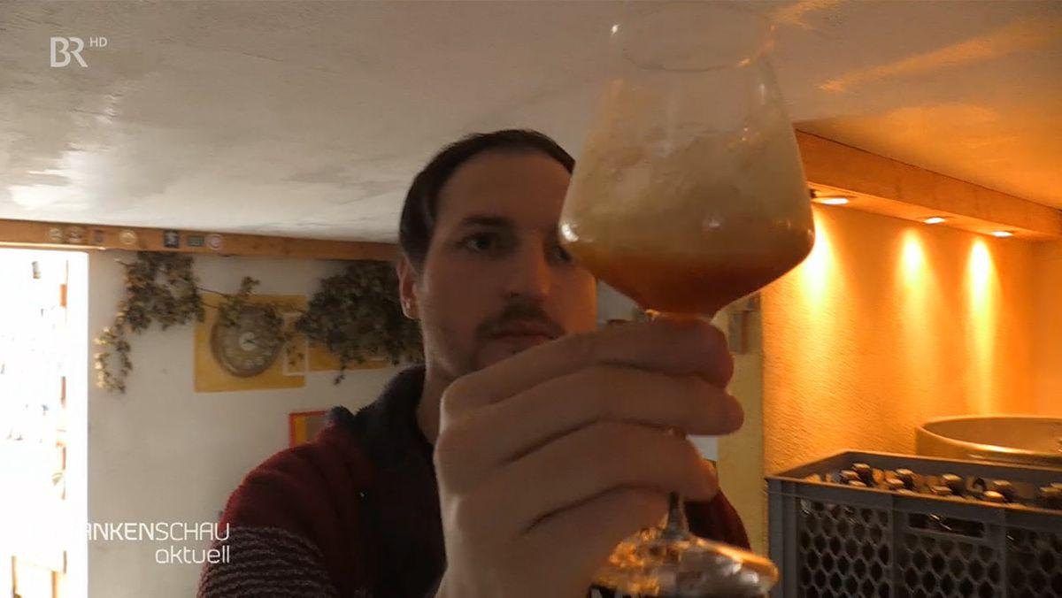 Ein Mann hält ein Glas Bier in die Höhe und betrachtet es.