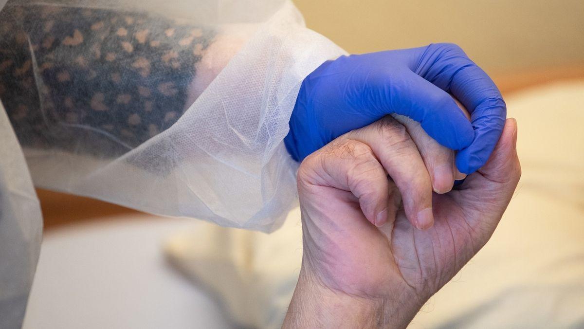 Pflegekraft mit Überwürf und Handschuh gesichert umfasst die Hand eines alten Menschen