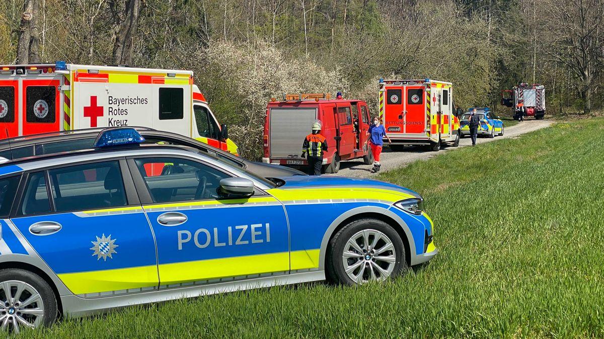 Mehrere Autos von Einsatzkräften stehen auf einem Feldweg.