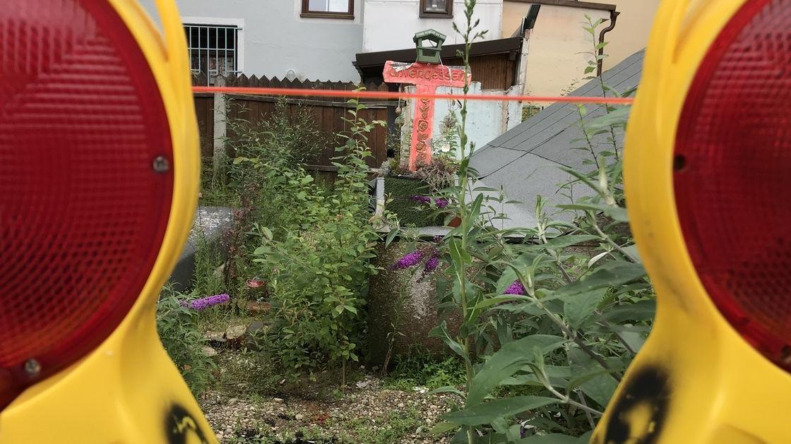 """Ein rotes Kreuz mit der Inschrift """"Unvergessen"""" erinnert an das illegal abgerissene Uhrmacherhäusl in Giesing."""