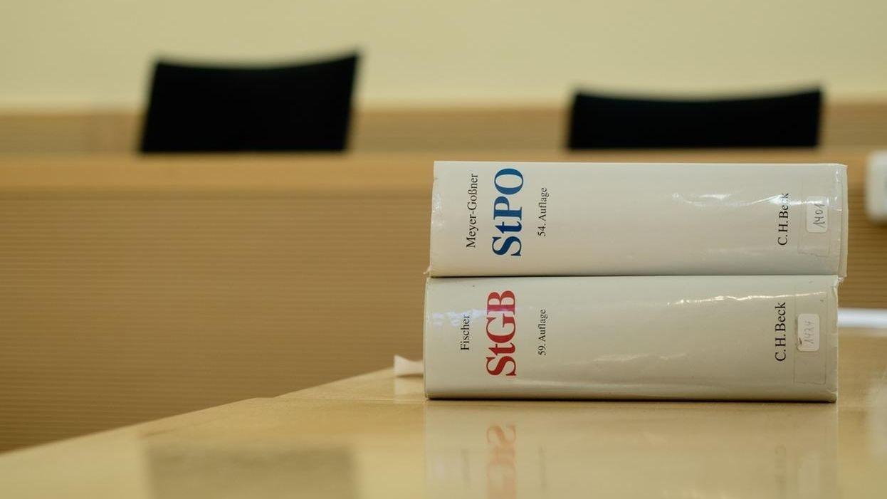 Ein Strafgesetzbuch und die Strafprozessordnung liegen in einem Gerichtssaal auf dem Tisch.