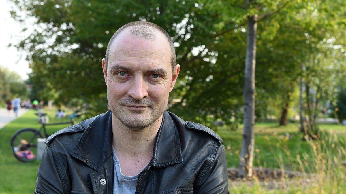 Ein kurzhaariger Mann in Lederjacke sitzt in einem Park und schaut in die Kamera