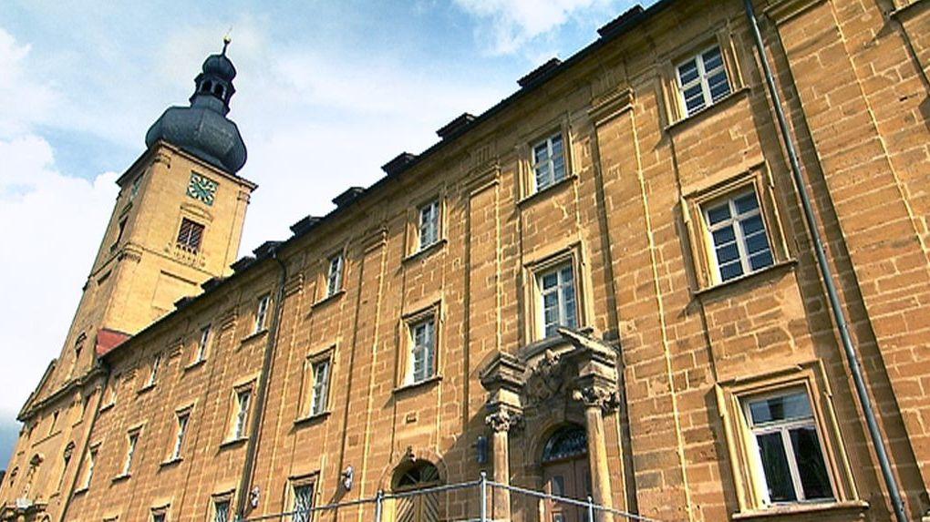 Die Sandsteinfassade des ehemaligen Klosters Weißenohe mit dem Kirchturm in Hintergrund.